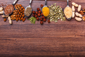 Assorted nuts on wooden surface. peanuts, almonds, hazelnuts, pumpkin seeds, walnuts, rice , buckwheat. Top view with copy space.