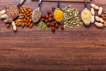 Assorted nuts on wooden surface. peanuts, almonds, hazelnuts, pumpkin seeds, walnuts, rice, buckwheat. Top view with copy space.
