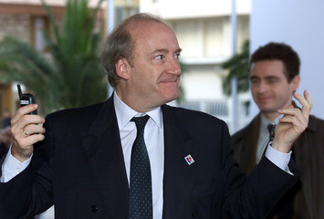 French Foreign Minister Hubert Vedrine shrugs when asked when the meetings will end, as he arrives f..