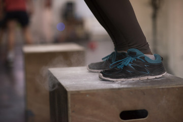 black woman is performing box jumps at gym
