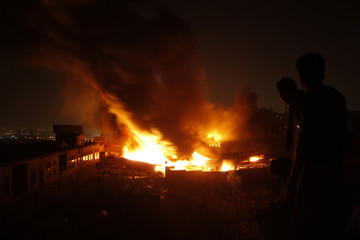Onlookers stand as fire engulfs a plastics factory in Sanaa