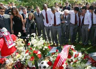 Portugal champion soccer team Benfica's players mourn over the tomb of Hungarian teammate Miklos Feher.