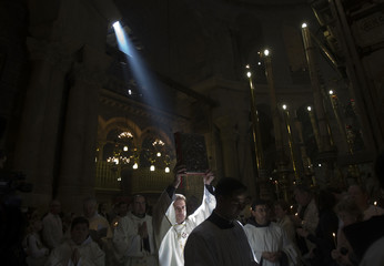 A member of the Catholic clergy holds up a bible during Easter Sunday mass in Jerusalem