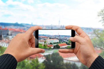 Man taking photo with smartphone of city skyline