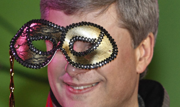 Canada's PM Harper poses with masquerade ball mask at Quebec's Carnaval