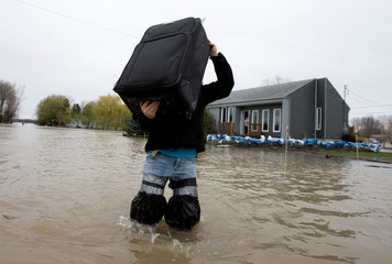 A resident removes belongings from his  home in a flooded residential neighbourhood in Rigaud, Quebec