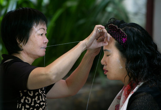 WOMAN PRACTICING TRADITIONAL FACIAL HAIR REMOVAL IN GHANGZHOU.