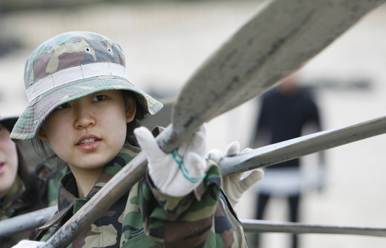 A female student learns how to row a rubber dinghy at a military training camp for civilians organised by South Korean marines in Pohang