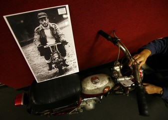 A photograph of John Lennon is displayed on a Monkey Bike he co-owned with Ringo Starr at Bonhams auction house in central London