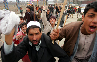 Afghan protesters run waving sticks in Kabul