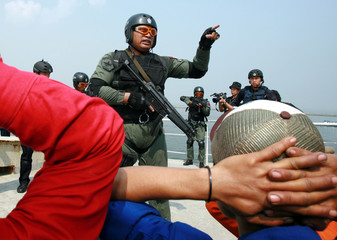 Singaporean and Indonesian navy soldiers arrest mock criminals during a joint naval exercise in Jakarta