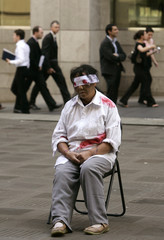 Falun Gong practitioner wearing fake bloodied bandages sits in chair in central Sydney