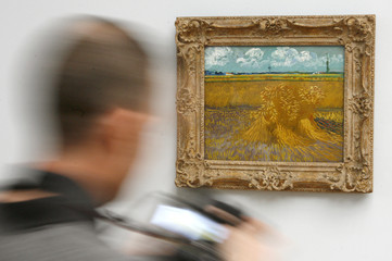 A photographer checks the display of his camera after taking a picture of the painting 'Wheatfield with Sheaves' from 1888 by late Dutch artist van Gogh out at a wall at the Kunstmuseum Basel in Basel