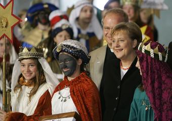 German Chancellor Angela Merkel sings with carol singers during a reception in the Chancellery in Berlin