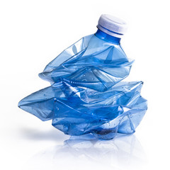 Crushed blue plastic bottle on white background. Still-life picture taken in studio with soft-box.