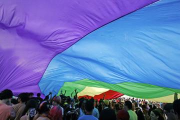 Participants under a rainbow flag walk down Atlantica Avenue in Copacabana beach during the annual ...