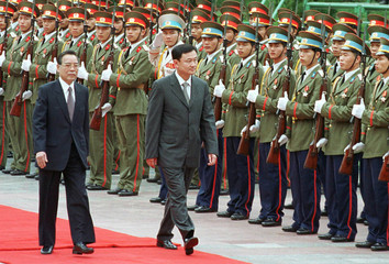 THAI PRIME MINISTER THAKSIN SHINAWATRA WALKS PAST HONOUR GUARD WITH VIETNAMESE COUNTERPART.