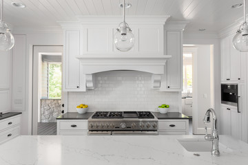 White Kitchen Detail in New Luxury Home with Oven and Range, Hood, Sink, and Pendant Lights