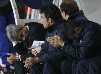 Paris St Germain coach Lacombe and team staff react during soccer match against Hapoel Tel Aviv in the UEFA Cup Group G match in Paris