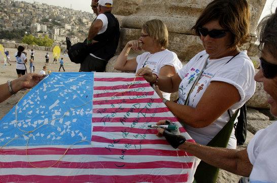 Denmava of U.S., member of Follow the Women Foundation, reads message written on kite depicting U.S. flag at Amman Citadel