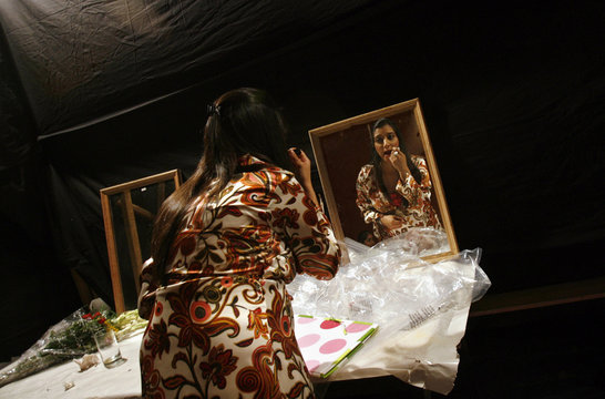 A pregnant model applies make-up in the dressing room during a maternity fashion show organised by a newly launched company which caters to pregnant women in New Delhi