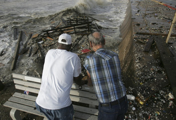 Men look over sea wall at debris caused by Hurricane Ike in Galveston