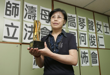 Gao, mother of jailed Chinese journalist Shi Tao, holds a trophy during a news conference in Hong Kong