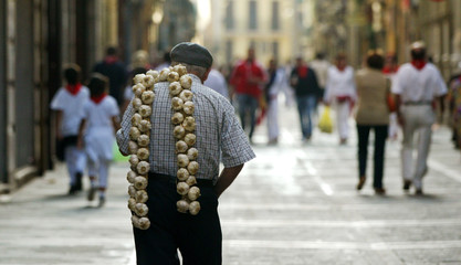 A man carries a string of garlic on his shoulder through the old part of town during San Fermin Festival in Pamplona