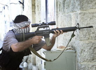 A PALESTINIAN GUNMAN TAKES POSITION IN THE WEST BANK TOWN OF BEIT JALA.