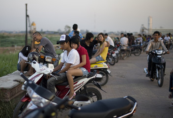 Young Cambodian couples gather on a board-walk near the banks of the Tonle Sap river during sunset in Phnom Penh