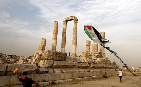 Jordanian boy flies kite depicting Palestinian flag, which belongs to members of Follow the Women Foundation, at Amman Citadel