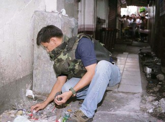 A PHILIPPINE POLICEMAN COLLECTS BOMB FRAGMENTS AFTER DETONATING IT IN MANILA.