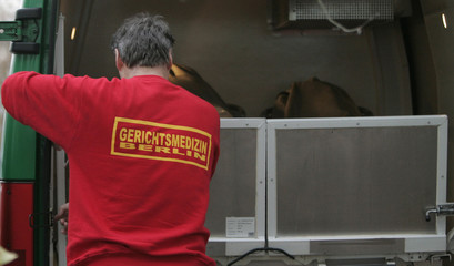 A forensic doctor loads a body into a vehicle at an apartment building in the Berlin district of Marzahn