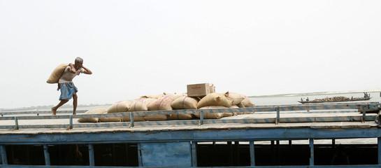 Labourer loads a sack of rice on a boat on the banks of river Brahmaputra in Dhubri