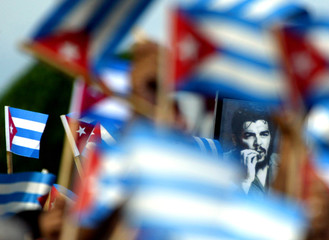 """A picture of late guerrilla leader Ernesto """"Che"""" Guevara is held high by Cubans during a rally in ..."""