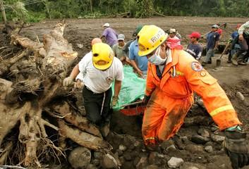 Guatemalan rescue workers carry the body of a mudslide victim in Maya Indian village Panabaj, Guatemala