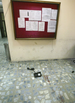 A telephone is seen lying near a bloodstain on the floor inside the building of the Higher Education Ministry in Baghdad