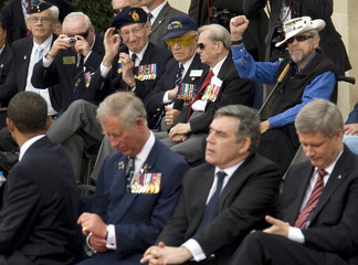 Canadian Normandy campaign veteran Stuart and an unidentified U.S. veteran gesture  to U.S. President Obama at the U.S. military cemetery in Colleville-sur-Mer
