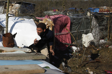 """An asylum seeker leaves his makeshift shelter in a wood named """"jungle"""" near the harbour of Calais"""