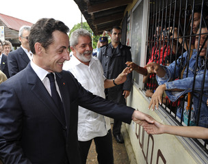 France's President Sarkozy and his Brazilian counterpart President Lula da Silva shake hands with residents in Saint Georges de l'Oyapock