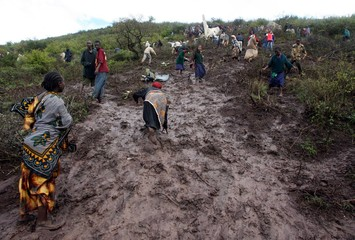 Kenyans climb uphill through the mud to the site where a Kenyan Y-12 military plane crashed in Marsabit