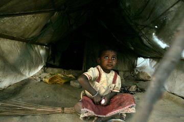 A child of Indian construction labourers sits in her tent at the construction site of a new shopping..