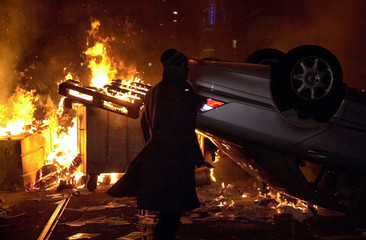 AN ANTI-GLOBALISATION PROTESTER WALKS PAST A BURNING CAR DURING RIOTS IN ZURICH.