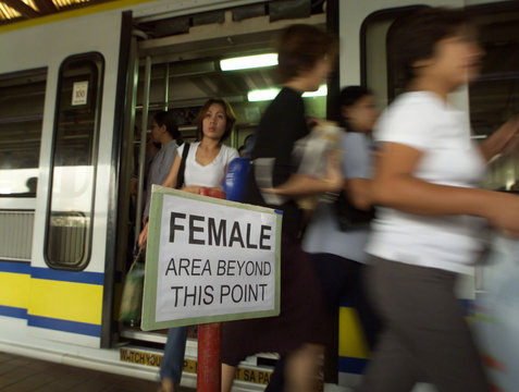 FILIPINA PASSENGERS STREAM OUT OF A RAIL CAR DURING RUSH HOUR INMANILA.