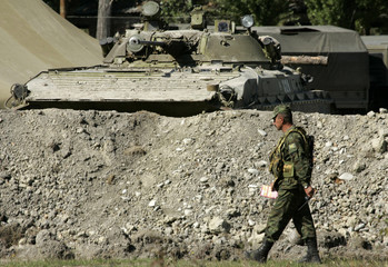 A Russian soldier walks at a checkpoint in the village of Karaleti