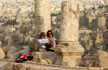 Members of the Follow the Women Foundation rest upon arriving on their bicycles at the Amman Citadel