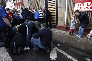 """A woman and a child laugh as local men scrum together to try and grab the beribboned leather ball during the annual """"Fastern Eve Handba"""" event in Jedburgh's High Street in the Scottish Borders"""