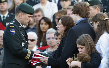 Wife of Master Warrant officer Mario Mercier, Lucie Ardouin, receives the Canadian flag from an officer after the funeral of her husband in Quebec City