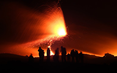 Tourists watch Mount Etna spew lava on the southern Italian island of Sicily