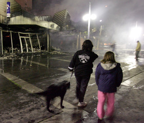 Residents look at the burnt out commercial centre Evreu west of Paris